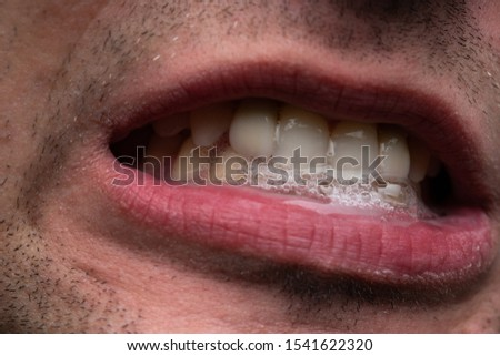 Image of young man with saliva, showing teeth Royalty-Free Stock Photo #1541622320