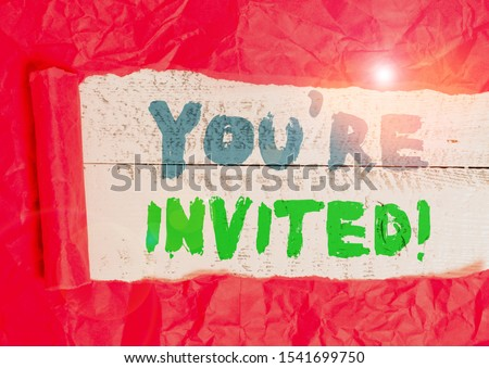 Conceptual hand writing showing You Re Invited. Business photo showcasing make a polite friendly request to someone go somewhere Cardboard which is torn placed above a wooden classic table. #1541699750