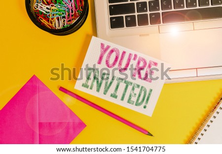 Handwriting text You Re Invited. Concept meaning make a polite friendly request to someone go somewhere Laptop pencil sheet clips container spiral envelope colored background. #1541704775