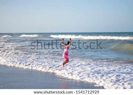 A girl frolicking in the ocean on the beach. #1541712929