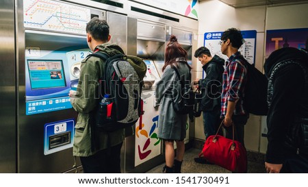 TAIPEI, TAIWAN. DEC 30, 2017: Passengers buy train ticket at the ticket machine with people waiting in line at the Taiwan underground train station. Mass transit in Taipei, Taiwan.  #1541730491