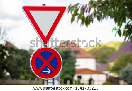 Two traffic sign on top of each other. A triangular sign means to pay attention to the right of way. The round sign means a stop in front of the sign. Blurred background with beautiful bokeh.