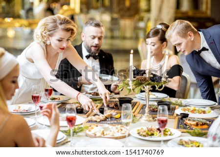 Elegantly dressed group of people having a festive dinner at a well-served table with tasty dishes during New Year Eve at the luxury restaurant #1541740769