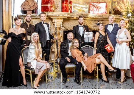 Staged group photo of an elegant well-dressed people near the beautifully decorated fireplace with christmas tree and presents during a New Year celebration #1541740772