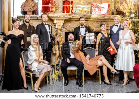 Staged group photo of an elegant well-dressed people near the beautifully decorated fireplace with christmas tree and presents during a New Year celebration #1541740775
