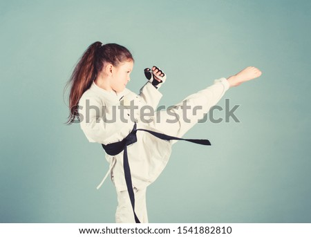 Karate gives feeling of confidence. Strong and confident kid. She is dangerous. Girl little child in white kimono with belt. Karate fighter ready to fight. Karate sport concept. Self defence skills. #1541882810