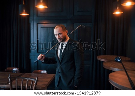 Young man in formal clothes stands with golf club in hand indoors. #1541912879