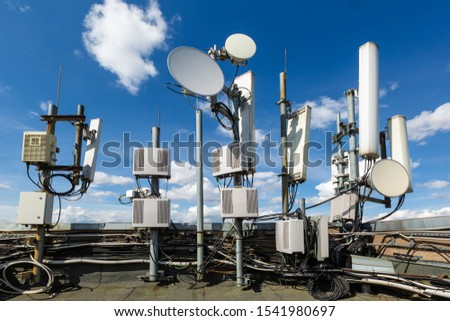 Metal constructions for telecommunication data equipment , radio panel antennas, outdoor remote radio units, power cables, coaxial cables, optic fibers are installed on the roof of building. Outside Royalty-Free Stock Photo #1541980697