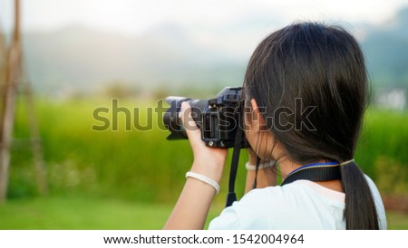 The girl is taking pictures with a DSLR. The girl took pictures with happiness Use a digital camera. Asian girl learning to use dslr camera in the garden.