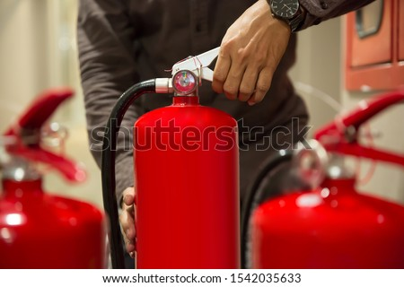 Fire extinguishers,Close-up  engineers hands are squeezing the Handle on the fire extinguisher. #1542035633