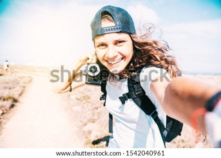 Beautiful slender young girl in a baseball cap takes a selfie during summer vacation. Witn photo camera, blogger lifestyle concept