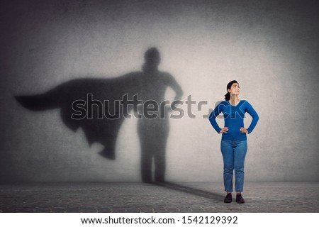 Brave woman keeps arms on hips, smiling confident, casting a superhero with cape shadow on the wall. Ambition and business success concept. Leadership hero power, motivation and inner strength symbol. #1542129392
