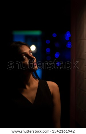 Portrait of an young and attractive Indian Bengali girl in black western dress standing in light and shadow. Indian lifestyle. #1542161942