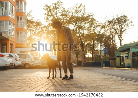 Photo of stylish woman walking dog in the evening on city background at sunset. Lady walking a puppy on a leash. Evening walk with your favorite. #1542170432