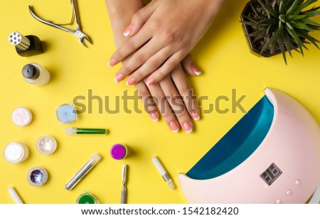Composition for nail care, female young hands, French manicure, gel polish, lamp for nails and equipment for nail care. Flat lay photo. #1542182420