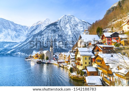 Classic postcard view of famous Hallstatt lakeside town in the Alps with traditional passenger ship on a beautiful cold sunny day with blue sky and clouds in winter, Salzkammergut region, Austria #1542188783