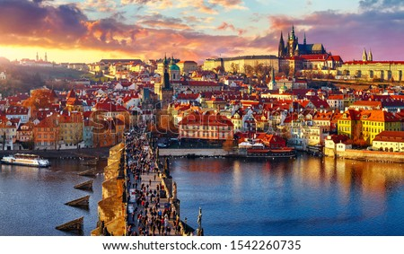 Panoramic view above at Charles Bridge Prague Castle and river Vltava Prague Czech Republic. Picturesque landscape with sunset old town houses with red tegular roofs and broach tower. #1542260735