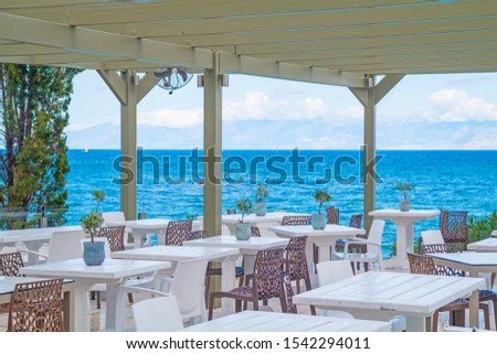 Beautiful tropical restaurant and beach with turquoise water. Corfu island, Greece. #1542294011