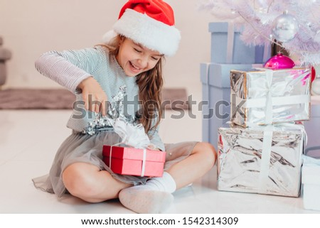 Full-body photo of super excited young girl opening a christmas present while sitting on the floor in lotos position. #1542314309