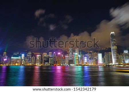 HONG KONG -29 JUN 2019- A view by night of the evening light show on the modern Hong Kong skyline seen from the Kowloon side across the Victoria Harbor. #1542342179