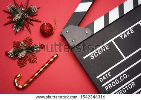 Filmmaker clapperboard with christmas decorations on red background. A Christmas movies and holiday classic cinema and TV flicks conceptual #1542346316