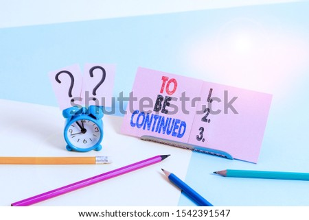 Conceptual hand writing showing To Be Continued. Business photo text indicate that the story continues in the next episode Mini size alarm clock beside stationary on pastel backdrop. #1542391547