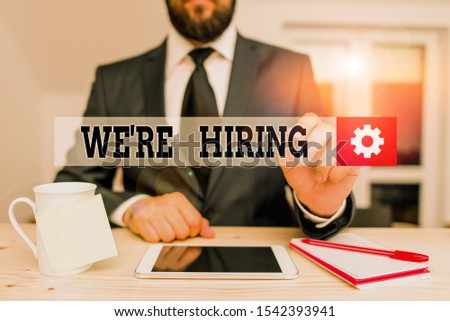 Handwriting text We Re Hiring. Concept meaning recently employ someone or pay him to do particular job Male human wear formal clothes present presentation use hi tech smartphone. #1542393941