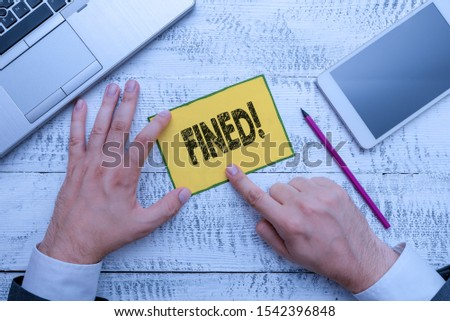 Handwriting text Fined. Concept meaning clarify beer by causing precipitation of sediment during production Hand hold note paper near writing equipment and modern smartphone device. #1542396848