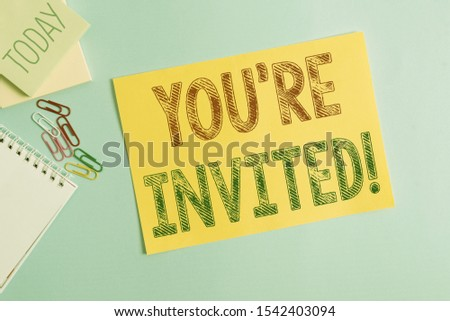 Conceptual hand writing showing You Re Invited. Business photo showcasing make a polite friendly request to someone go somewhere Cardboard and writing equipment placed above pastel backdrop. #1542403094