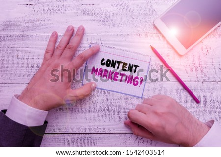 Conceptual hand writing showing Content Marketing question. Business photo showcasing involves creation and sharing of online material Hand hold note paper near writing equipment and smartphone. #1542403514