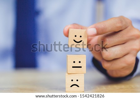 customer pressing smiley face emoticon on wood cube, Service rating, satisfaction concept. #1542421826
