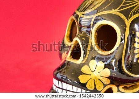 Gold and black Skull on red background at right and 3 quarters rotation getting out of picture close up