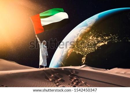 emirati man holding UAE flag standing on the moon Royalty-Free Stock Photo #1542450347