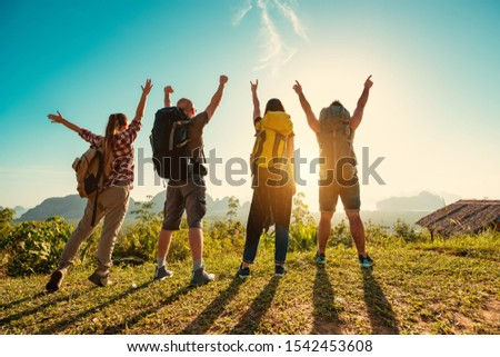 Four travelers or hikers stands with backpacks at sunrise against islands and sea #1542453608
