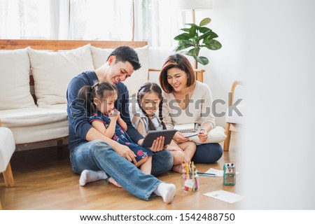 Happy Asian family using tablet, laptop for playing game watching movies, relaxing at home for lifestyle concept Royalty-Free Stock Photo #1542488750