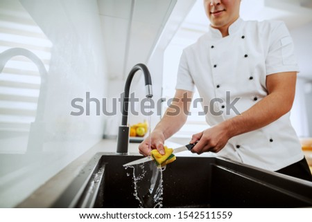 Cropped picture of caucasian chef in uniform washing kitchen knife in sink. Kitchen interior.