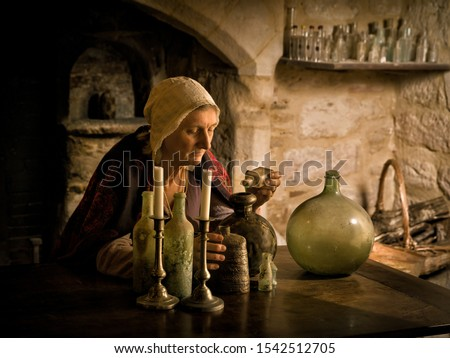 Woman in medieval outfit working as an alchemist or witch in the kitchen of a French medieval castle - with property release Royalty-Free Stock Photo #1542512705