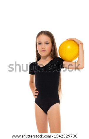 Picture of a gymnast girl in white short socks and black trico full height stands with yellow ball in her hands isolated on a white background