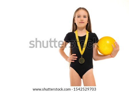 Picture of a gymnast girl in white short socks and black trico full height stands with yellow ball in her hands and a medal around her neck isolated on a white background