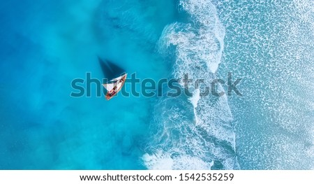 Wave and boat on the beach as a background. Beach and waves from top view. Turquoise water background from top view. Top view from drone. Travel - image #1542535259