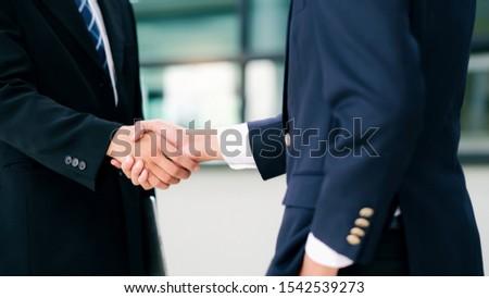 Businessmans handshake. Successful businessmen handshaking after good deal. Business partnership meeting concept. #1542539273