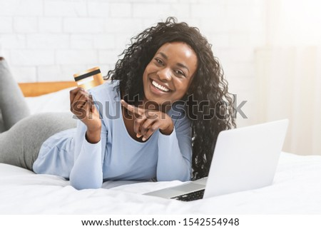 African woman laying on bed at home, shopping online, using laptop and pointing at credit card, copy space #1542554948