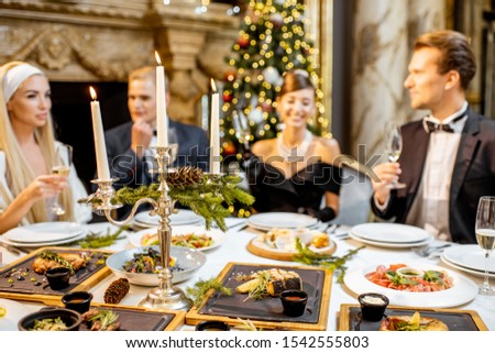 Elegantly dressed group of people having a festive dinner at a well-served table, celebrating New Year holiday at the luxury restaurant #1542555803