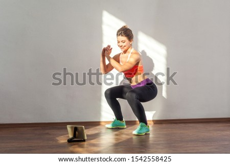 Positive sportive woman with bun hairstyle and in tight sportswear doing squatting sit-up exercise while watching training video on tablet. indoor studio shot illuminated by sunlight from window #1542558425