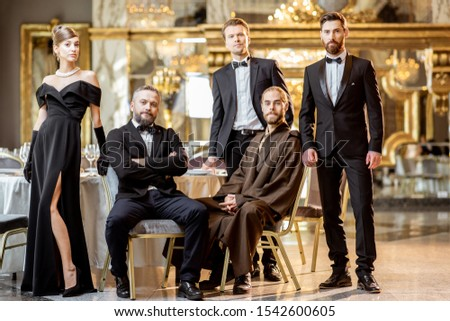 Staged group photo of an elegant people strictly dressed standing at the luxury restaurant hall #1542600605