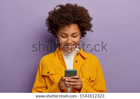 Photo of glad female blogger types text content for web publication, focused in smartphone, wears yellow shirt, checks received notification, smiles gently, isolated over purple studio wall. #1542612323
