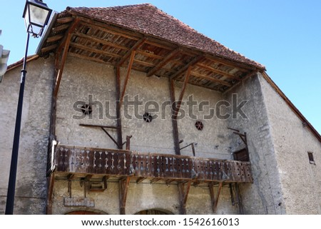 The wooden framework and balcony, and the hexagonal opening for air of an old farm in the village (Valeyres-sous-Rances, Vaud, Switzerland                                #1542616013