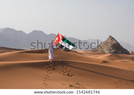 Arab man holding the UAE flag in the desert celebrating UAE national day and Uae flag day. Royalty-Free Stock Photo #1542681746