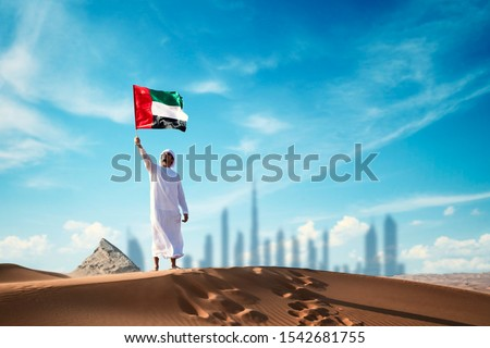 Arab man holding the UAE flag in the desert celebrating UAE national day and Uae flag day. #1542681755