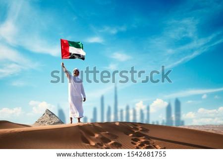 Arab man holding the UAE flag in the desert celebrating UAE national day and Uae flag day. Royalty-Free Stock Photo #1542681755